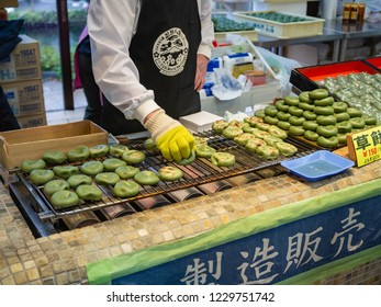Oshino Hakkai, Japan - October 19, 2018: Seller grill Kusamochi, or mochi with red green bean paste at Oshino Hakkai, Japan.