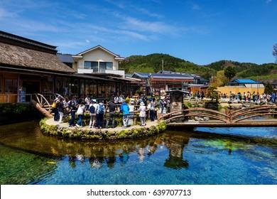 OSHINO, JAPAN - MAY 02, 2017: Tourists visit Oshino Hakkai, a small village in the Fuji Five Lake region, located between Lake Kawaguchiko and Lake Yamanakako.