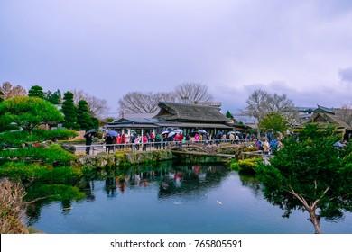 Oshino, Japan - November 2017: Tourists visit Oshino Hakkai, a small village in the Fuji Five Lake region, located between Lake Kawaguchiko and Lake Yamanakako. Select focus.