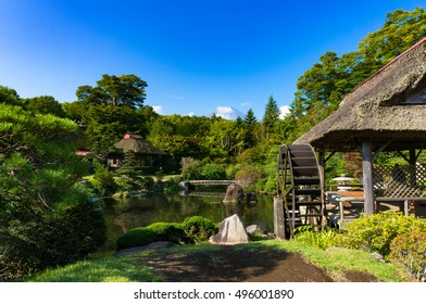 Oshino, Japan - September 2, 2016: Oshino Hakkai, Fuji Five Lakes. Japan countryside landscape of historic thatch roof farmhouses and pond with water wheel, watermill and Mount Fuji on background
