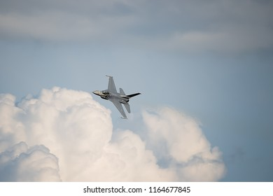 Oshkosh, WI - 28 July 2018:  A F-16 flying falcon starting to turn with clouds in the background at the EAA airshow.