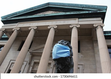 Oshkosh, WI / USA - May 13, 2020: The Oshkosh Public Library's infamous lions wear face masks as a way to remind its visitors to do so during the COVID-19 pandemic. The library's doors remain closed.