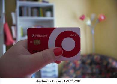 Oshkosh, WI / USA - May 20, 2020: A woman with pink nails holds a Target REDcard Debit Card in front of her colorful bedroom items obtained from the chain retailer. It provides store-wide savings.