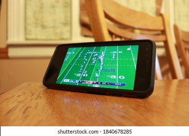 Oshkosh, WI / USA - October 25, 2020: An NFL game streams on a mobile device that is propped up on a table amid the coronavirus pandemic.