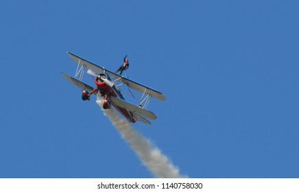 Oshkosh, Wisconsin / USA  - July 24, 2017: Wing walker performance by Greg and Ashley Shelton using a red white and blue Stearman at airshow