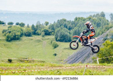 Osinniki, RUSSIA - July 28, 2017: Open competitions in motocross, motorbike and motorcycle races off-road cross-country. Close-up of a child kid motorcyclist rider jump.