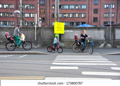 OSLO - AUGUST 17: Family with bikes crossing the road on August 17, 2013 in Oslo, Norway. About 70 percent of the population of Norway have a bycicle