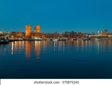 Oslo City Hall in twilight. Lights reflected in the sea.