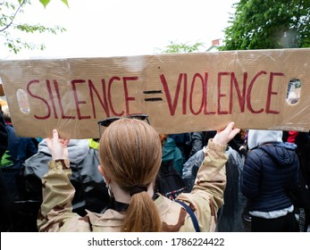 """OSLO - JUNE 5, 2020: A sign reads, """"Silence = Violence"""" as thousands march from the U.S. embassy to Norwegian parliament to show solidarity with Black Lives Matter, Oslo, Norway, June 5, 2020."""