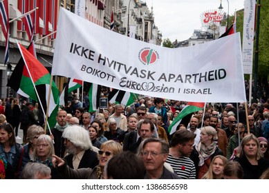 """OSLO - MAY 1, 2019: Marchers carry a banner reading """"Don't Whitewash Apartheid: Boycott Eurovision in Israel"""" during a May Day march in Oslo, Norway, May 1, 2019."""