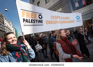 "OSLO - MAY 1: Activists carry a banner in English and Norwegian: ""Free Palestine: Stop Buying Occupation Products"" at the annual May Day march in Oslo, Norway, May 1, 2017."