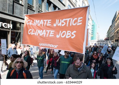 "OSLO - MAY 1: A Greenpeace activist holds a sign reading ""Climate Justice, Climate Jobs"" at the annual May Day celebration in Oslo, Norway, May 1, 2017."