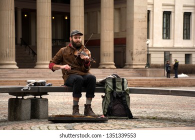 Oslo, Norway, 02/25/2019, Street musician, Street musician playing violin on Oslo street.A man plays the violin.