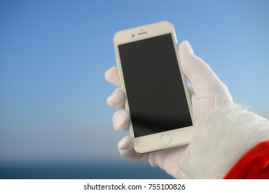 Oslo Norway - 03 November 2017: Santa Claus holding Apple Iphone 8 smartphone on Christmas sun light blue sky. Person showing mockup display app, closeup view. Sunny seasonal festive time photography