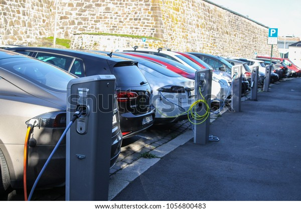 Oslo, Norway - 2016-10-05 : Electric cars plugged in and charging at a car park on the street in Oslo, Norway