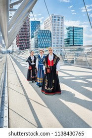 Oslo, Norway - 8/12/2012: Three women in Norwegian national costumes (bunad) standing on a bridge in modern urban environment