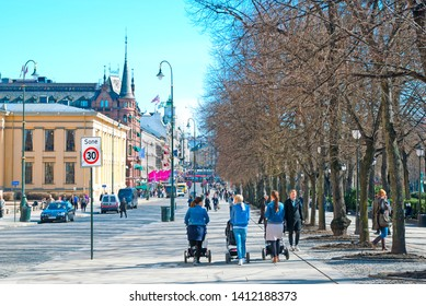 OSLO, NORWAY - APRIL 12, 2010: Young mothers with baby carriages near University of Oslo. Street Karl Johans gate in the center of capital. It is a main street of the city