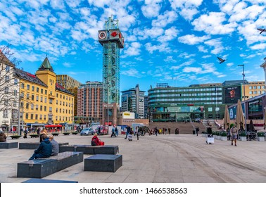 OSLO, NORWAY, APRIL 16, 2019: People are strolling on a square in front of the railway station in Oslo, Norway