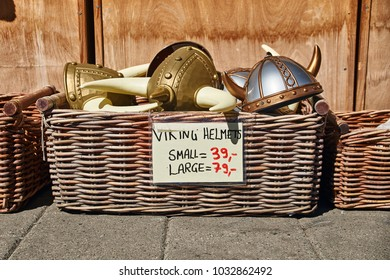 Oslo, Norway: April 26 2017 - Toy horned helmets in traditional Norwegian style in wicker basket are sold on the street in front of a souvenir gift shop.