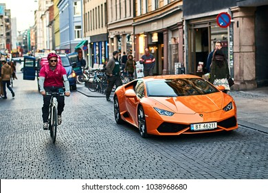 Oslo, Norway: April 26 2017 - Orange Lamborghini Huracan LP 580-2 Spyder car released circa 2016 in Italy parked on the street with a bicycle courier passing by.