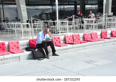 OSLO, NORWAY - AUGUST 16: Unidentified man reading near Opera House on 16 August 2012 in Oslo, Norway.