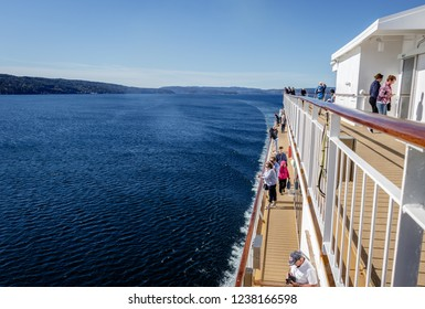 OSLO, NORWAY - AUGUST 5, 2018: People on the deck of the Color Lines Fantasy cruise ferry. Enjoying the sun and the beautiful Oslo fjord early mornings after the night trip from Kiel, Germany
