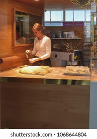OSLO, NORWAY - CIRCA AUGUST 2017: unidentified beautiful Norwegian young woman baking bread and brioches for sale