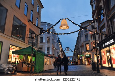 OSLO, NORWAY - December 10, 2018: Man and woman are walking down Karl Johan's street, near the main train station in Oslo. Oslo's main street is decorated for Christmas.