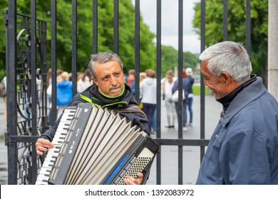 Oslo, Norway -Jule, 2016: Street musician enthusiastically plays the accordion, the viewer listens to him attentively and smiles. Accordion player near the sculpture park Gustav Vigeland, Oslo, Norway