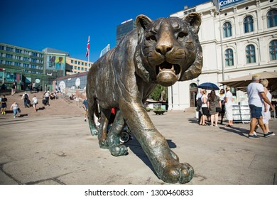 OSLO, NORWAY - JULY 04, 2018: The tiger sculpture in front of Oslo Central Station People on scquare. Sunny summer day