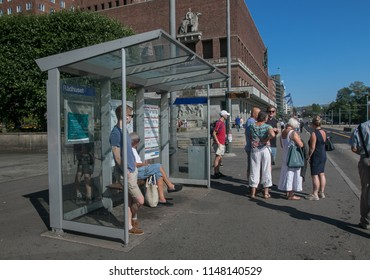 Oslo, Norway, July 21, 2018: People are waiting for a bus at a bus stop near City Hall.