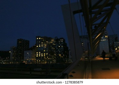 Oslo, Norway – July 21, 2018: Akrobaten pedestrian bridge in Bjorvika district at night. Modern business architecture in the center of Oslo.  Bridge across the tracks of Oslo central station.