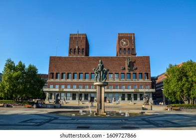 OSLO, NORWAY - JULY 23 2014: fountain and bronze statue with women and children in the front of Oslo City Hall (Radhus) - houses the city council, city administration, and art studios and galleries.