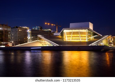 OSLO, NORWAY - JULY 24, 2018: Oslo Opera House (Operahuset),  home of The Norwegian National Opera and Ballet and the national opera theatre with Barcode buildings in background at night