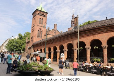 OSLO / NORWAY - JUNE 08 2019: People walk Oslo's main street Karl Johans . The fire guard (Brannvakten) in connection with the Bazar - built in redeveloped red brick in neo-romantic style.