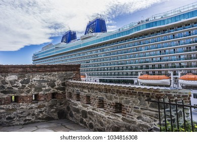 OSLO, NORWAY - JUNE 14, 2017: Luxury Cruise ship Britannia moored below the fortress of Akershus Fastning in Oslo Fjord.