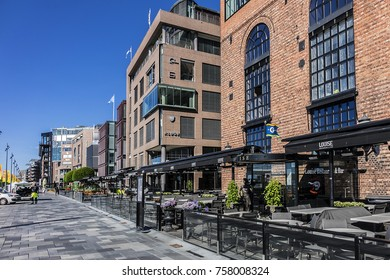 OSLO, NORWAY - JUNE 14, 2017: Aker Brygge - most popular neighbourhood in central Oslo: Shopping, dining and entertainment area. Aker Brygge is known for its strip of restaurants along the boardwalk.
