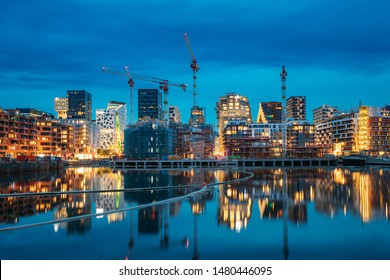 Oslo, Norway - June 25, 2019: Night View Embankment And Residential Multi-storey House In Gamle Oslo District. Summer Evening. Residential Area Reflected In Sea Waters.