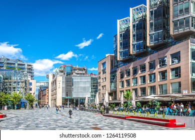 Oslo, Norway - June 5th 2018 - People walking in at Aker Brygge neightbourhood in Oslo in a summer blue sky day with modern buildings and restaurants in Oslo