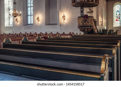 Oslo, Norway - Mar 27 2018 : Row of Wooden church pew bench with lantern decoration at Christian church
