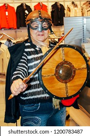 Oslo, Norway - May 02 2007: Senior woman in a Viking helmet with a sword and a shield in a souvenir shop