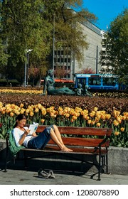 Oslo, Norway - May 02 2007: Woman sitting on a park bench and reading a book