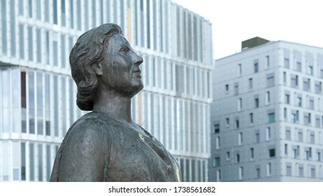 Oslo, Norway - May 22, 2019: The statue of soprano singer Kirsten Flagstad is standing near the Oslo Opera house. In the background modern architecture buildings in the Bjørvika city district.