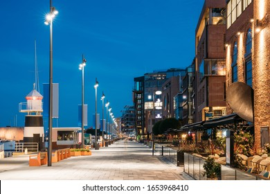 Oslo, Norway. Night View Embankment And Residential Multi-storey Houses In Aker Brygge District. Summer Evening. Residential Area Reflected In Sea Waters. Famous And Popular Place.