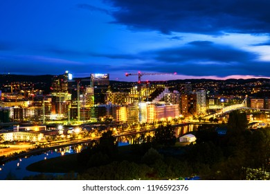 Oslo, Norway. A night view of Sentrum area of Oslo, Norway, with Barcode buildings and the river Akerselva. Construction site with sunset colorful sky