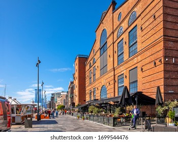 Oslo, Ostlandet / Norway - 2019/09/02: Panoramic view of modernistic Aker Brygge district of Oslo along Stranden boulevard at the Oslofjorden shore
