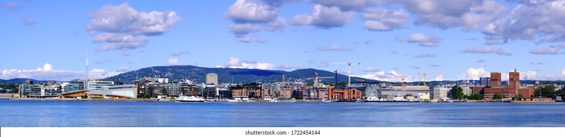Oslo, Ostlandet / Norway - 2019/09/02: Panoramic view of Oslo waterfront with City Hall, Aker Brygge and Tjuvholmen borough at Pipervika harbor