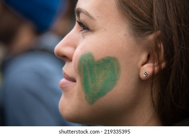 OSLO - SEPTEMBER 21: A woman has a green heart painted on her face as thousands march through downtown Oslo, Norway, to support action on global climate change, September 21, 2014.