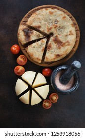 Ossetian pie with meat, sliced suluguni cheese and tomatoes. Flatlay on a dark brown metal background