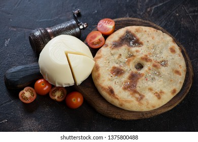 Ossetian pie with meat stuffing, suluguni cheese and tomatoes, studio shot on a dark brown stone surface